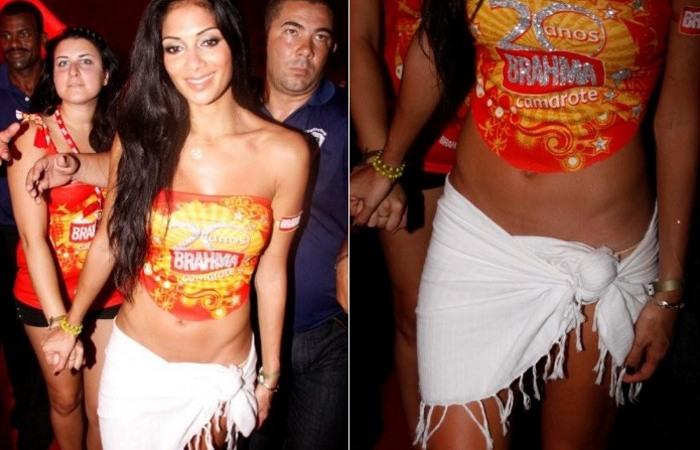 A vocalista do Pussycat Dolls, Nicole Scherzinger, apareceu bem soltinha e desinibida no camarote da cervejaria Brahma, na Marquês de Sapucaí. Tão tranquila e ambientada que nem reparou um detalhe estratégico no modelito que deixava aparecendo a barriga malhada - a calcinha cor da pele surgiu, apoteótica como uma comissão de frente, sob a canga sexy